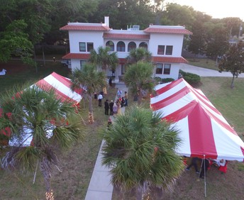 drone view of President Snow's residence; front lawn has 2 large red and white tents; formally dressed students mill about