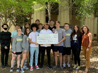 teacher and 13 Mass Media students holding large check in high school front yard