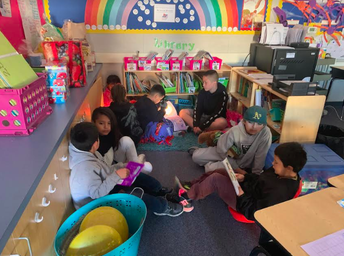 Upper grade students listening to Kindergarteners read to them.