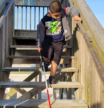Jayden walking down wooden stairs while using his cane