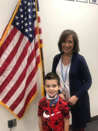 principal with student standing in front of flag