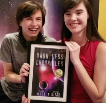 GHS Sophomore Willow Wren and her co-author pose with a framed picture of their book cover.
