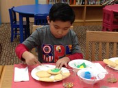Joe Anthony is using green to decorate his cookie.