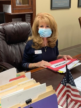 Dr. Neill in a mask at her desk
