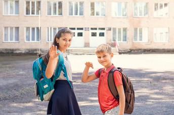 Two children waving bye.
