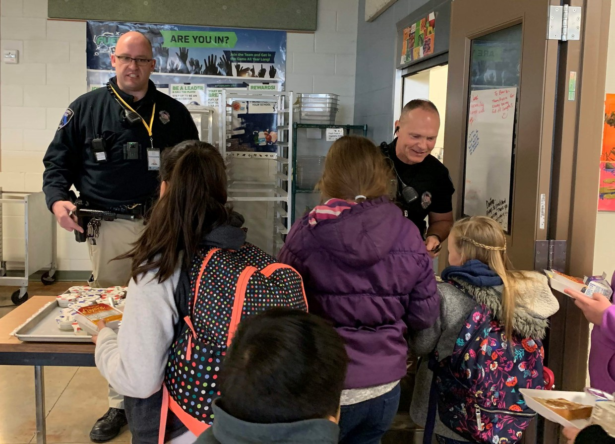 Officers serving students breakfast