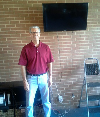 Volunteer Bible Study Leader Kent Carpenter poses in front of the TV he hung on the wall of the Wesley!