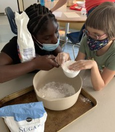 Jermeka and Arabella measuring sugar and flour to put in their bowl