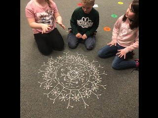 2nd grade creates symmetrical snowflakes!
