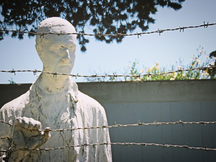 Statue of Holocaust prisoner next to barbed wire fence
