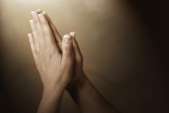 Hands held up together in prayer, palms together