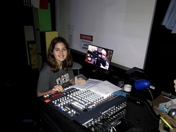 student smiles from the audio-video control panel in the lunchtime production of 7 ways to survive the zombie apocalypse