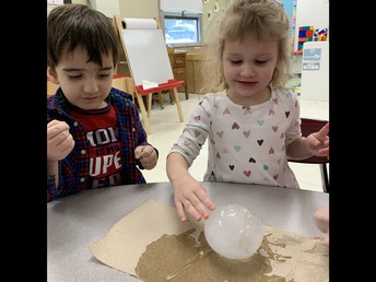 Miss Camille's Tiny Toppers Preschool students explore what happens when a water balloon is frozen.
