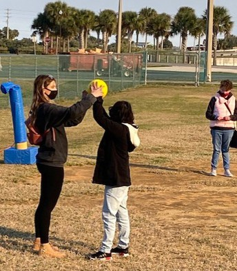 Ms. Lukic and a student are holding the yellow ball above the student's head