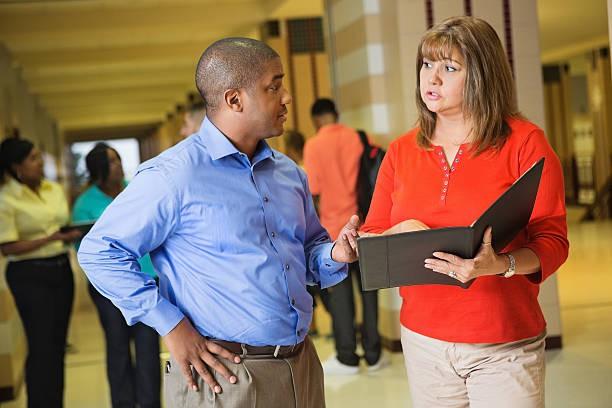 Two school administrators talking in a hallway