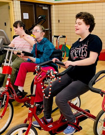 "Photo shows three young ladies on adapted bicycles after their ""cycling class"". Shown left to right at Brianna P, Annie K, and Marie G."