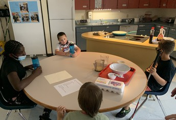 4 students sit spaced out around a circular table; a carton of eggs, several bowls and measuring cups are on the table, along with print and braille instructions