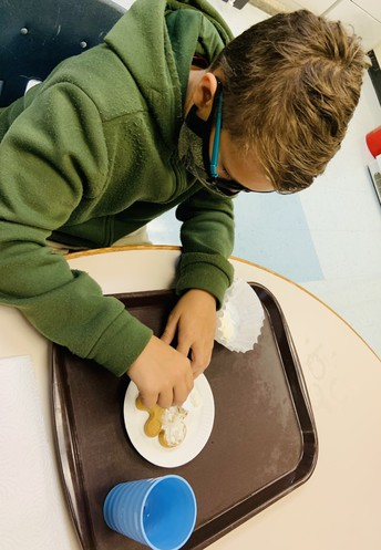 Student using a tray to help organize his cookie decorating supplies