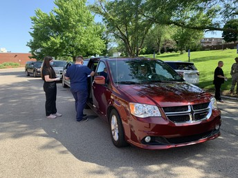 Health care workers provide vaccines to a family in a mini-van