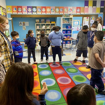 The class stands in a circle playing a game.