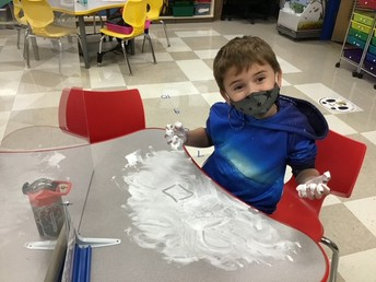 Student practicing shapes with shaving cream