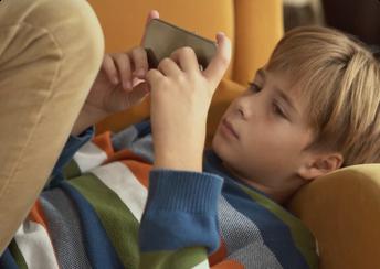 Sad child using cell phone