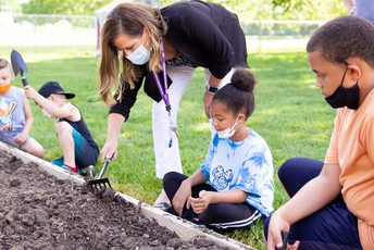 Instructor and young students plow in the community garden