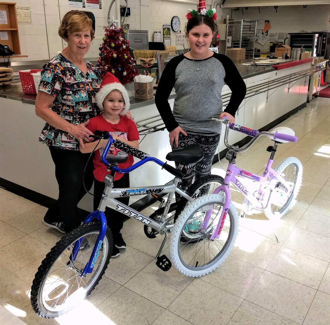 Park Elementary kitchen assistant Mrs. Tamara Peine with bike-winning students Dexter Clark and Addison Hope.
