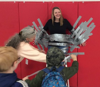 Picture of students duck taping Principal Alisa Simms to the wall.