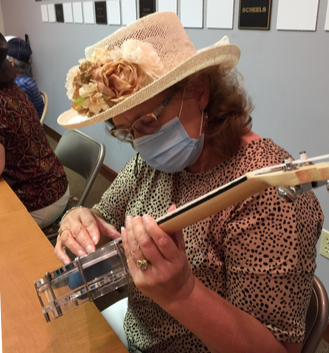A student in a lovely hat plays a ukelele.