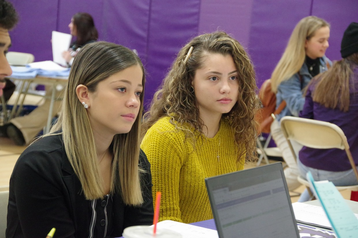 2 female high school students seated at table listening to college representative share information.