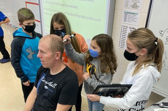 3 of Mr. Roozenboom's students work together to shave his head