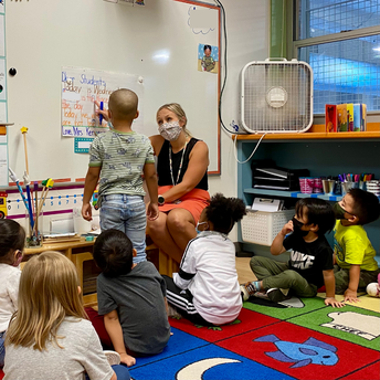 The class watches while a teacher and student point out specific letters on the morning message poster.