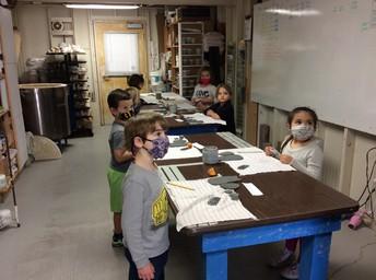 Kindergarten Class listening to Instruction in Ceramics Class.