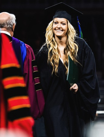 Shannon dressed in black graduation robe smiling as she walks onstage to receive her diploma