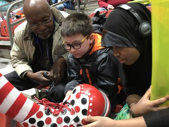 2018 at the Aladdin Shrine Circus.  Students Brian, Amina and a volunteer meet a circus clown, and explore his giant red and white shoe, with black and red polka dots.