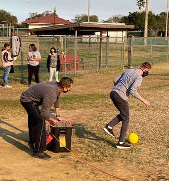 Mr. Puch encourages a student from behind as they attempt to kick the ball