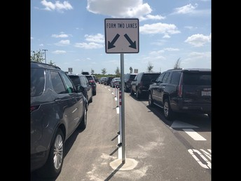 Please wait until you reach this sign before going into the left lane of the car rider line.