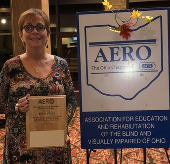 Mrs. Robin Finley is shown smiling and holding a plaque from recent Association for Education and Rehabilitation of the Blind and Visually Impaired of Ohio.