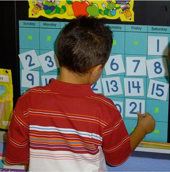 Boy in red striped shirt looking at calendar.