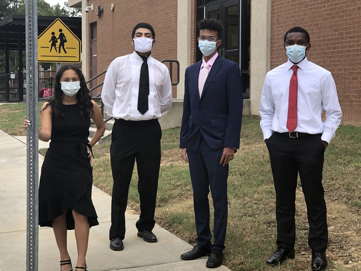 Four Maxwell students dressed professionally and wearing masks.