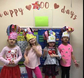 Kindergartners posing with their 100 days hats. Sign behind them says Happy 100 days.