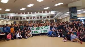 students with banner that says Go Wildcats and Novi Pride