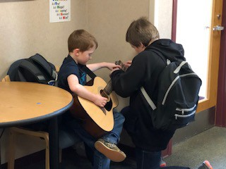 Teaching a schoolmate how to play the guitar