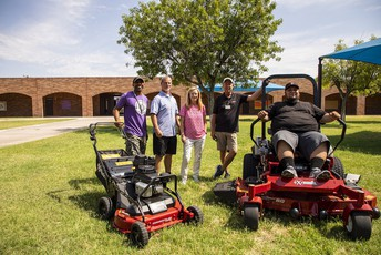 Bush principal Dr. Leslie Saulsby (left) poses with newly donated lawn mowers