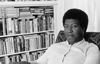 Octavia E. Butler sits smiling at the camera in front of a bookshelf filled to the brim with books.