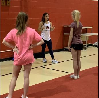 auburn cheerleader talking to two students