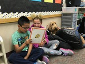 Partner reading with our therapy dog, Oliver