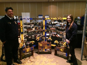 Hunter Lopez and Mikayla Haynes pose in front of the Gilbert FFA Chapter Display.